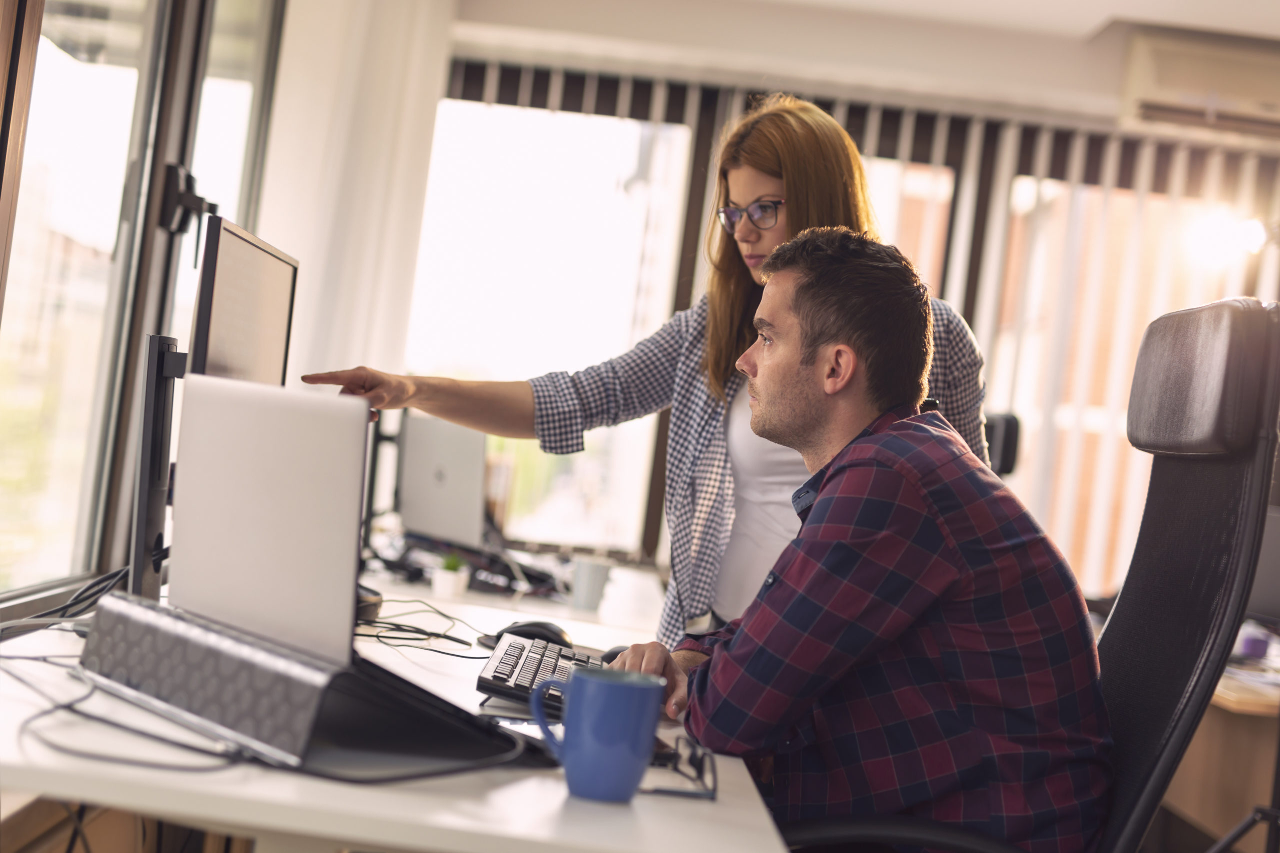 Two software developers working on a new project in a software developing company office. Focus on the woman poiting to the comuter screen